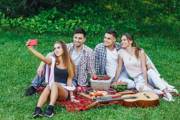 公園でピクニックを持つ幸せな若い友人。