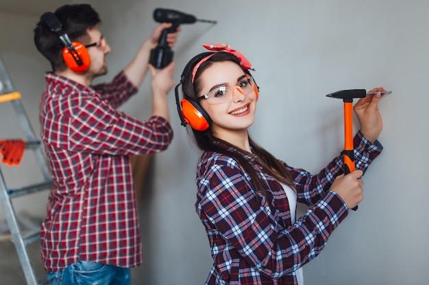 Позитивная девушка забивает гвоздь своим парнем, надевая красивое снаряжение