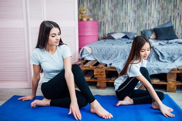 美しい若い女性と彼女の陽気な娘はマットで運動をしています。