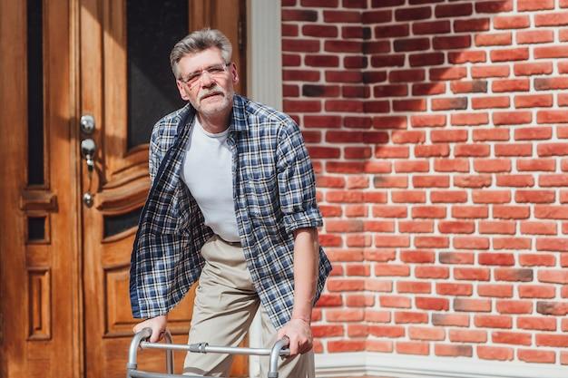 Старик держит на инвалидной коляске, глядя из камеры