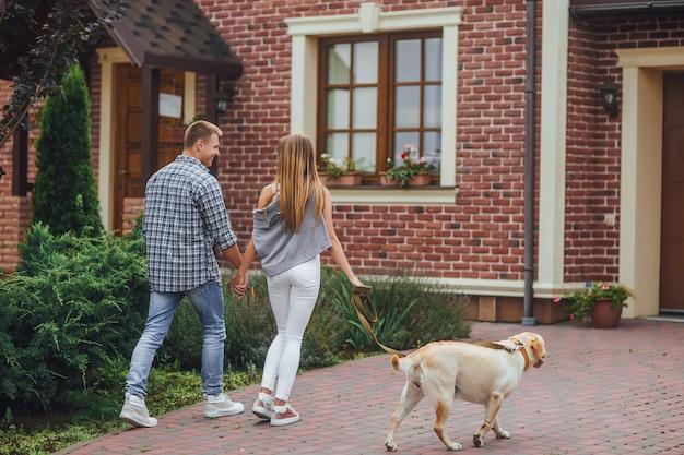 Успешная молодая пара прогулки с собакой возле дома.