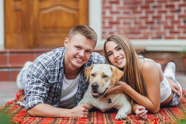 Счастливые улыбающиеся пара отдыхает во дворе с собакой.