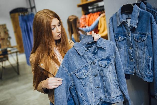 Красивая девушка на покупки, выбирая одежду в магазине.