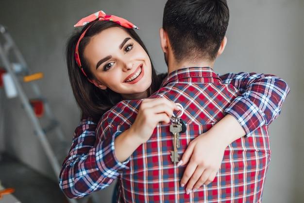 Женщина обнимает мужа, он купил новые апартаменты для своей пары
