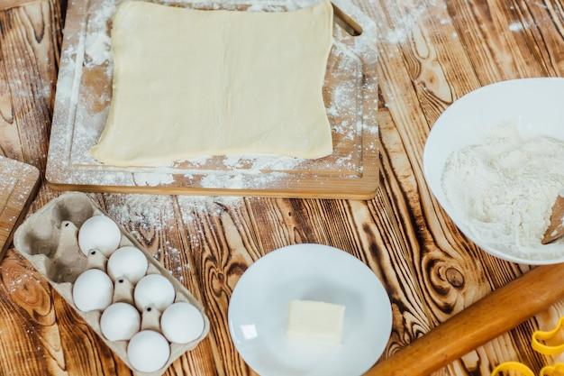 生地と木製のテーブルの麺棒。イースターのコンセプト