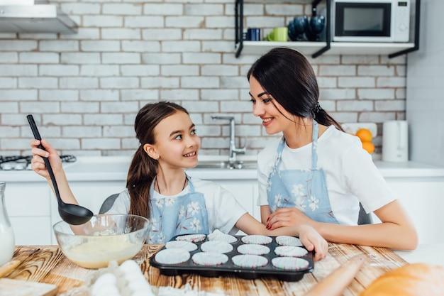 Готов к выпечке кексов. сестры смотрят друг на друга