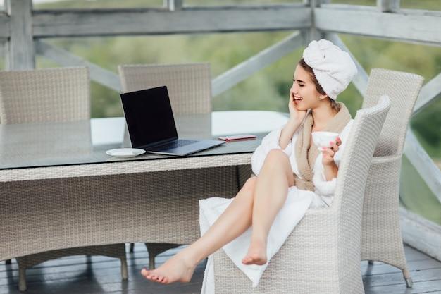 朝のオンライン。白いローブで彼女のラップトップで笑顔、かわいい女性はテラスに座っています。