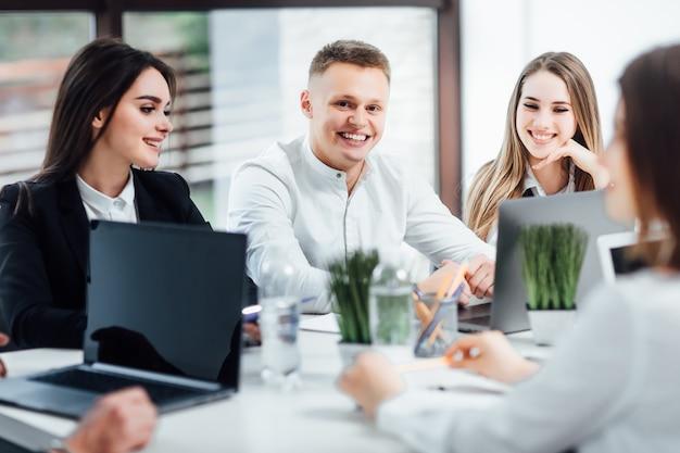 Веселые эмоции деловых людей сидят в офисе и работают с ноутбуком