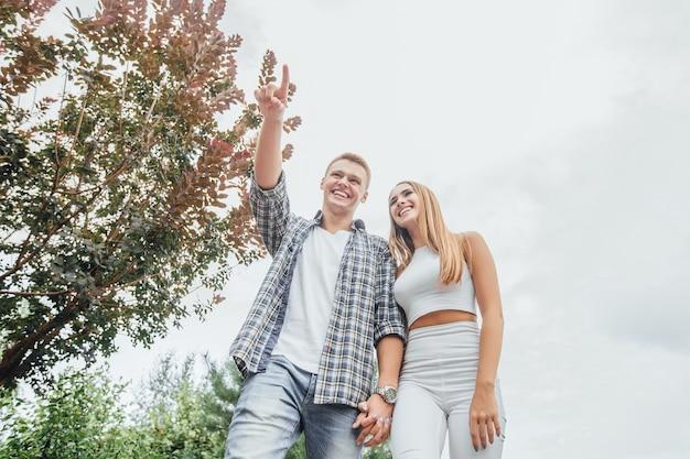 公園で一緒に若いカップル。野外を歩いているロマンチックなカップル。男は女の子に何かを示しています