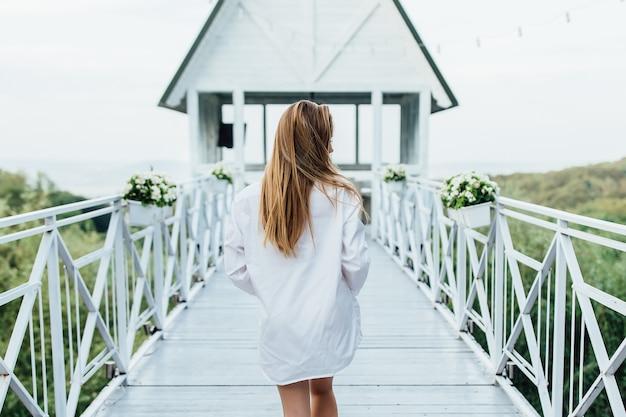背中の写真。リゾートの早朝のサマーテラス。歩いている白いシャツの女性。