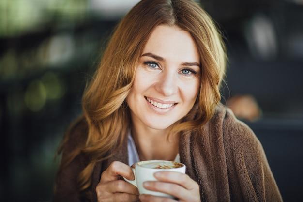 Красивая белокурая женщина средних лет накрывается поваром на летней террасе и отдыхает в кафе и пьет кофе.