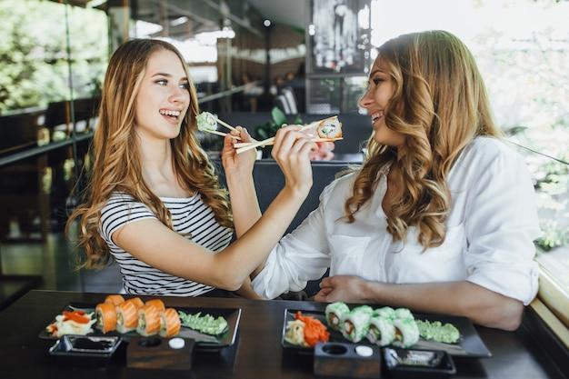 Обед в китайском ресторане на летней террасе. мама и ее молодая красивая дочь едят суши с китайскими палочками