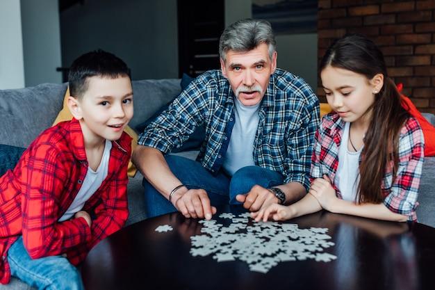 祖父と孫が家で遊んでいます。ジグソーパズルを組み立てる男と子供