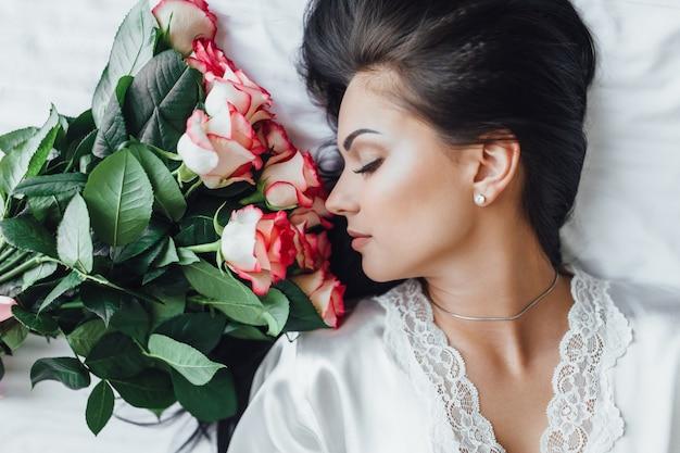 Утро красивой женщины в отеле с розами