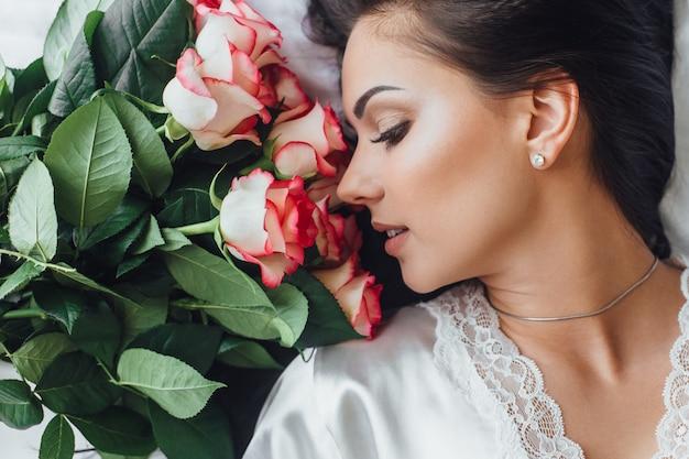 Утро красивой женщины в отеле с розами в постели, крупным планом фото