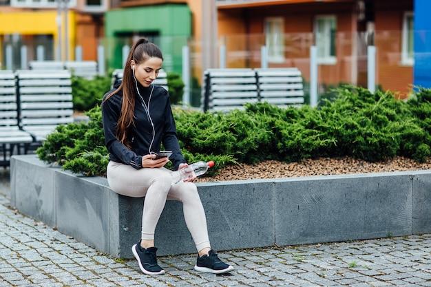 若いブルネットの女性はジョギングや水を保持した後リラックスしています。