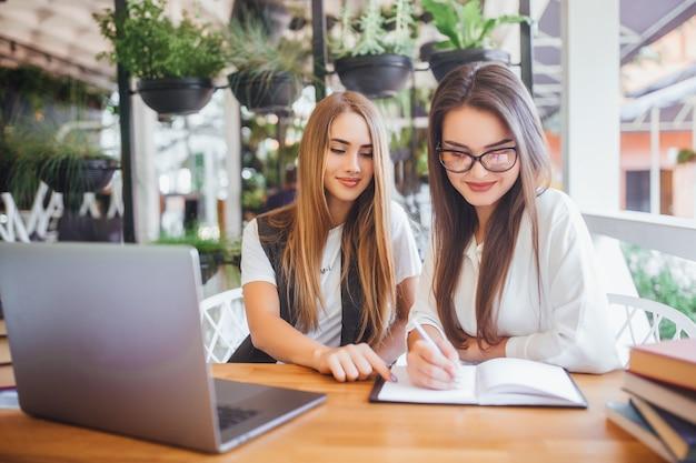 Две молодые красивые бизнесвумен обсуждают условия контракта сидя в кафе