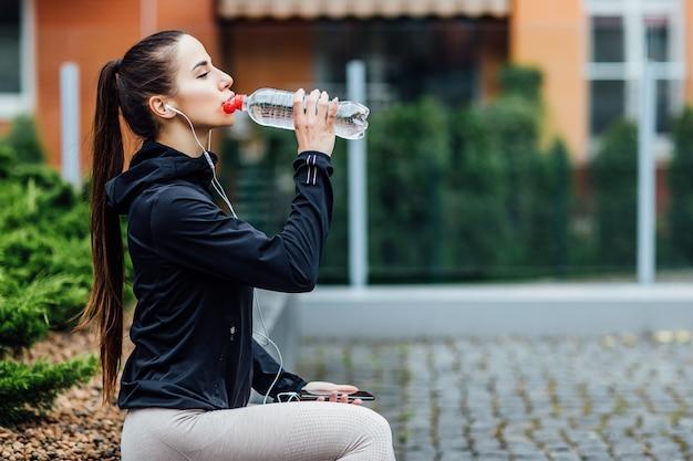 スポーツウェアの女性は、朝のランニングの後、新鮮な空気で水を飲む。
