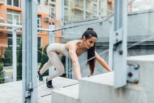都市の階段で腕立て伏せをしている強い女性。やる気のある女性のラテン系アスリートのトレーニング強度。