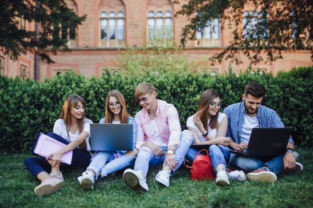 キャンパスに座ってラップトップを探している学生のグループ。