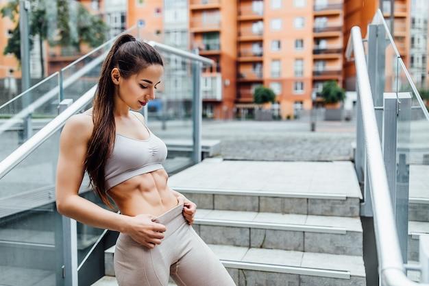 トレーニング後の公園で素敵な腹筋を持つ運動少女はリラックスします。美しいスポーツの女性。