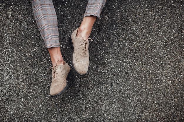Стильная обувь на ногах человека, сидящего на улице
