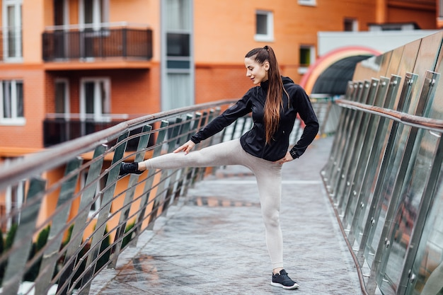 屋外の階段でストレッチ体操を行うフィットネス女性の肖像画。