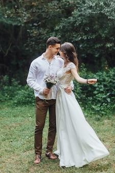 新婚夫婦を歩きます。自然の中で新郎新婦。結婚式の日。若いカップルの最高の日