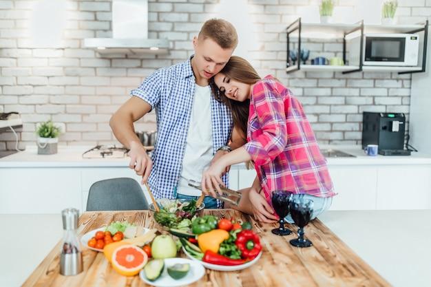 ロマンチックな若いカップルが一緒に台所で調理します。