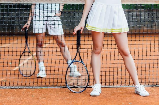 テニスプレーヤーがコートで試合をします。トリミングされた画像。