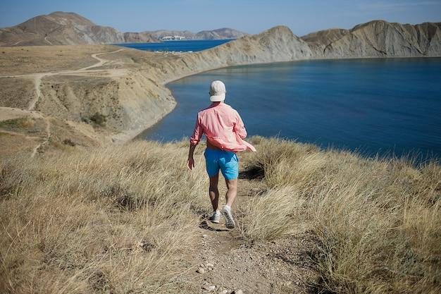 山の岸まで丘を歩いて若い男