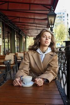 夢のような思慮深い視線でカフェのベランダでコーヒーを飲みながらベージュのコートを着た若い女性のストリートポートレート