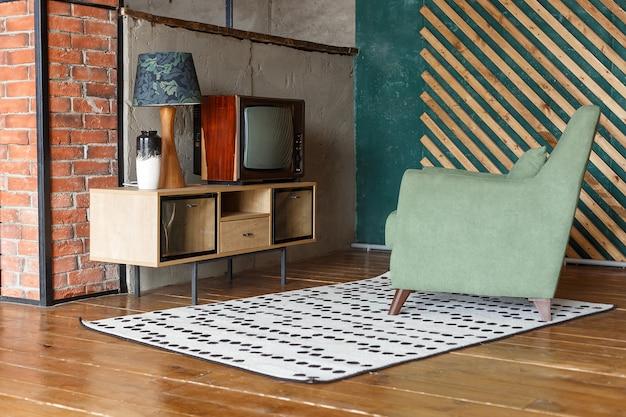 カーペット、昔ながらのアームチェア、レトロなテレビ付きのビンテージルーム