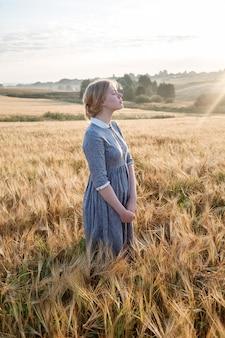 ゴールデンフィールドで青い昔ながらの屋外ドレスで素敵な幸せな若い女の子
