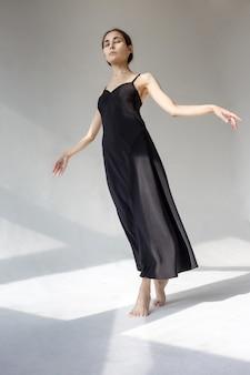 Худая азиатская балерина в черном платье стоит на белой полой циклораме в узоре света и тени. мир и радость