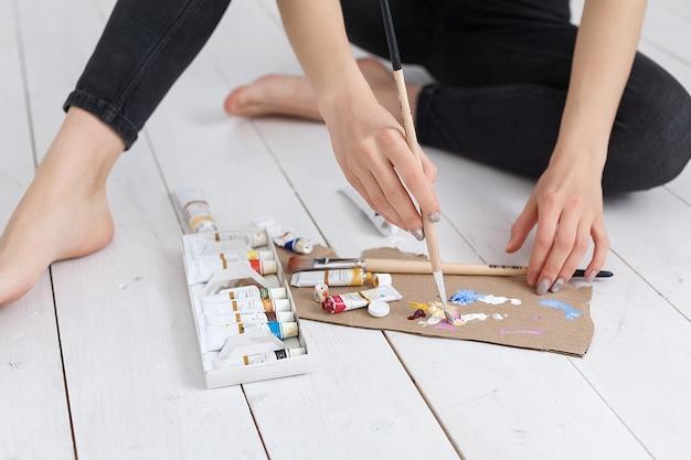 パレットの色を混ぜるブラシでアーティストの手をクローズアップ。アート、創造性、趣味の概念、アンチストレスアート療法。