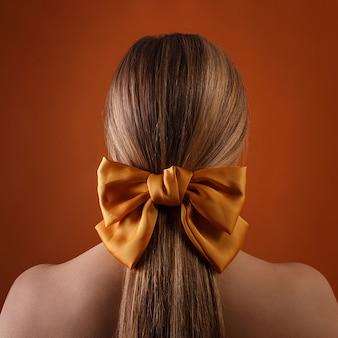 彼女の髪に弓を持つ女性