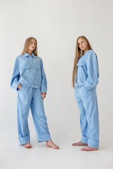 Две довольно молодые сестры-близнецы с длинными светлыми волосами, позирует на белом фоне в негабаритных одеждах. модная фотосессия