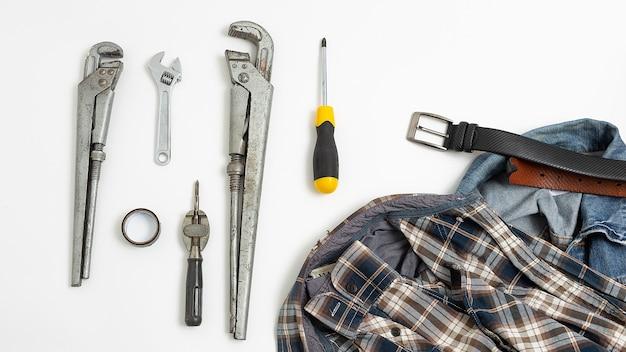 市松模様のシャツ、ジーンズ、革ベルト上面の近くのツール。メンズホビーフラットレイ