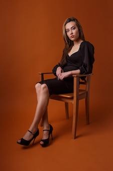 Красивая модель в черном платье и на высоких каблуках сидит в кресле