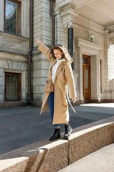 微笑んでいる女の子が日当たりの良い街-若い人たちの自由と幸福の概念の境界線の上を歩く