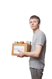 カートン募金箱に食料品を保持しているボランティア