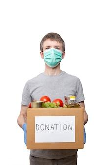 Волонтер в синих защитных перчатках держит продуктовый продукт в картонной коробке для пожертвований
