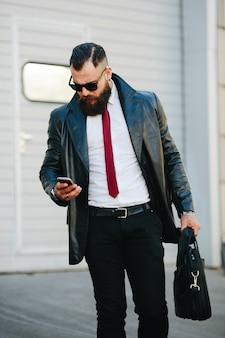 Человек в кожаном плаще проверяя его сотовый телефон