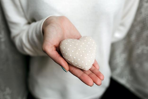 手の中にハート型の石を持つ女性
