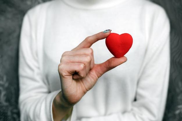 彼女の手に赤いハートを持つ女性