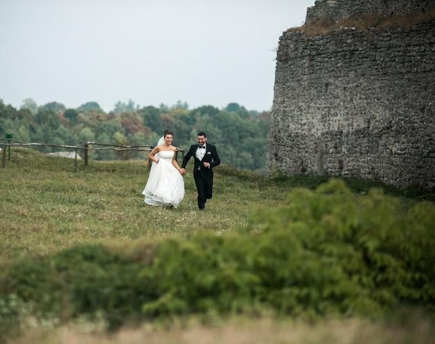 緑のフィールドを介して実行している新婚夫婦