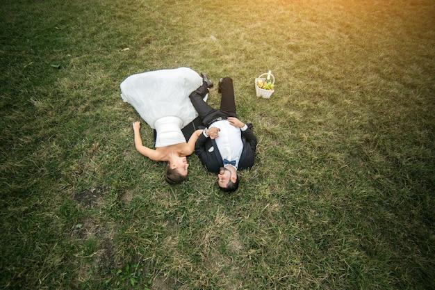 上から見た芝生の上に横たわっている若い夫婦