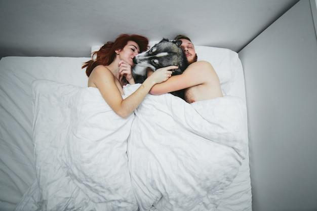 犬を抱いてベッドの中でカップル