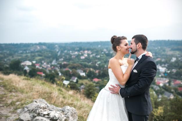 屋外でポーズ朗らか新婚夫婦